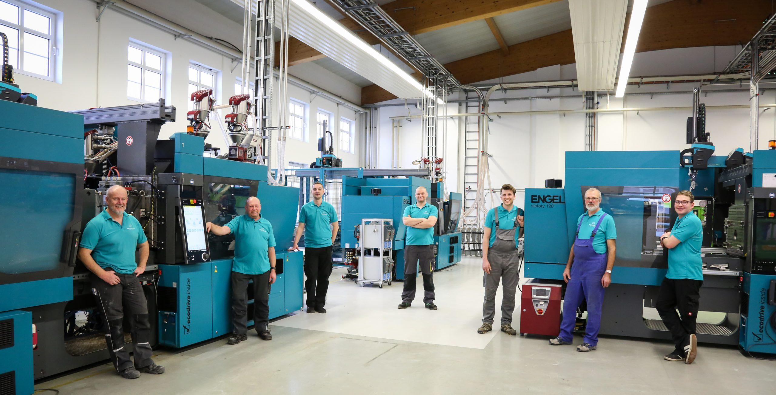 gesamte Team der Produktion vor dem Maschinenpark